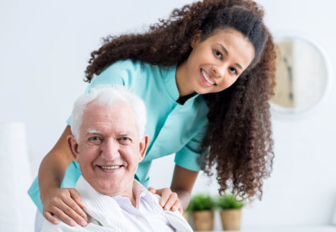 senior man and a caregiver smiling