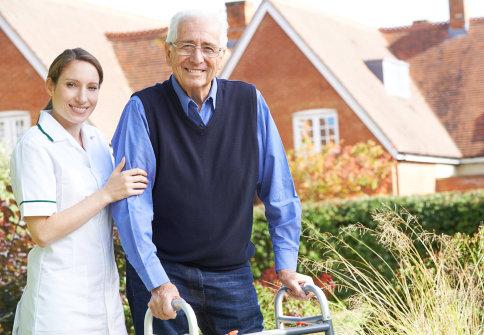 senior man and a caregiver outside senior home