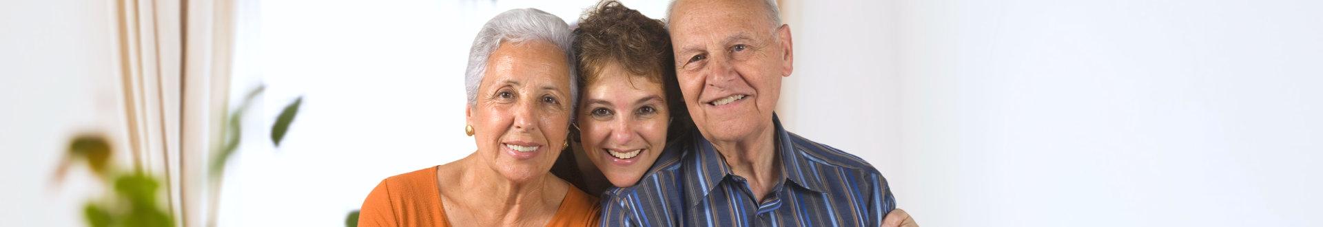 senior couple and their caregiver smiling