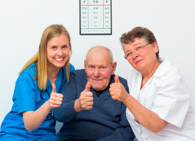 two caregiver and a senior man doing thumbs up